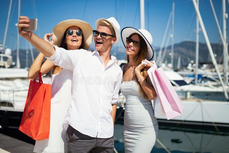 Konsumeryzm, przyjaciele, wakacje, podróży pojęcie Piękni ludzie cieszy się zakupy ma zabawę fotografia royalty free