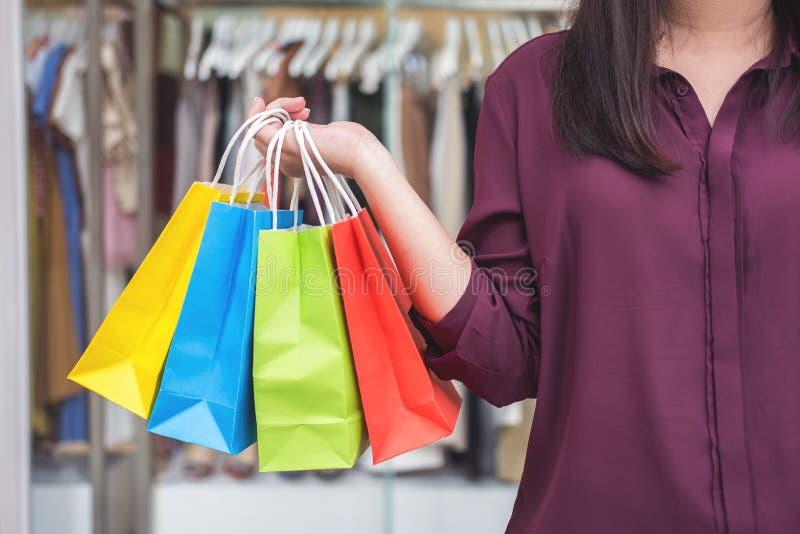 Konsumeryzm, robi zakupy stylu życia pojęcie, młodej kobiety pozycję i mień kolorowych torba na zakupy cieszy się w zakupy, zdjęcia royalty free