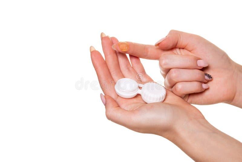 Kontaktöga Lens Närbild av kvinnahänder som rymmer den vita eyelensebehållaren arkivbild