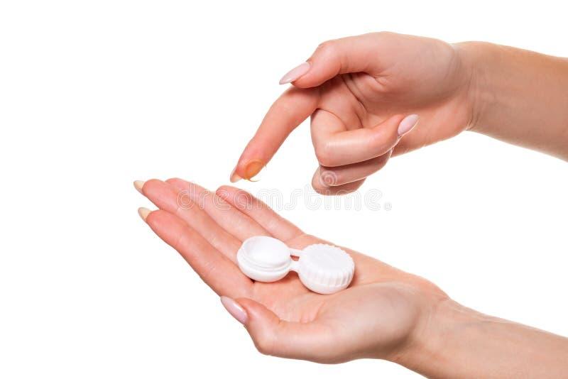 Kontaktöga Lens Närbild av kvinnahänder som rymmer den vita eyelensebehållaren royaltyfri bild