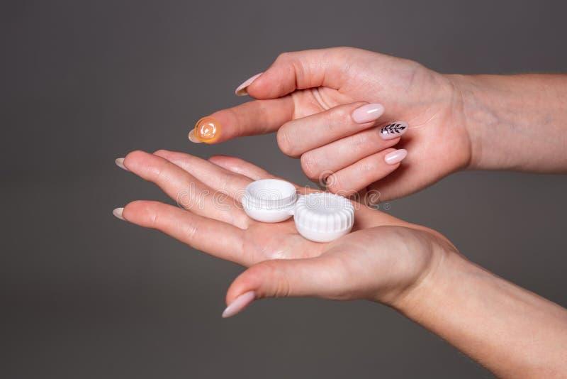 Kontaktöga Lens Närbild av kvinnahänder som rymmer den vita eyelensebehållaren royaltyfria bilder