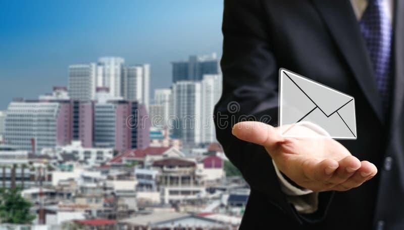 Kontakta oss begreppet, affärsman bär emailen med cityscapebakgrund royaltyfri bild