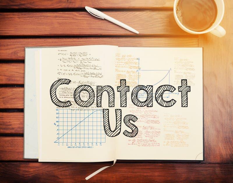 Kontakta oss: smsa inom anteckningsboken på tabellen med kaffe arkivbild