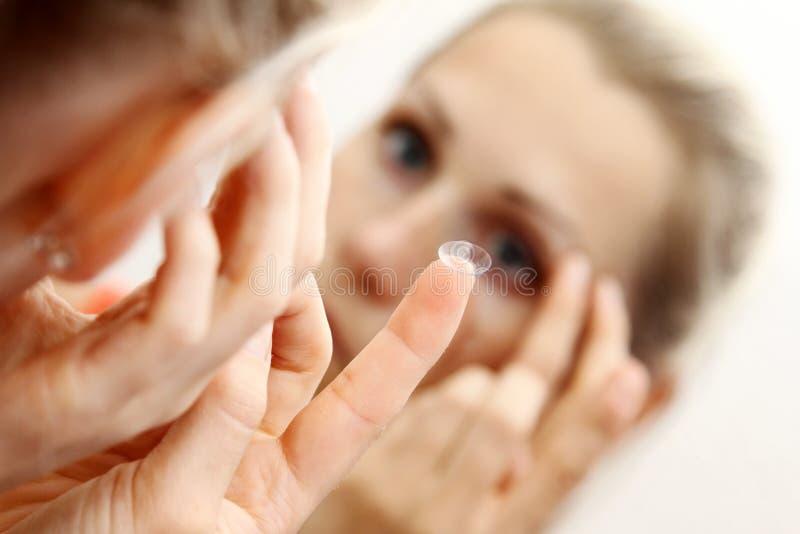 kontakten eye henne linsen som sätter kvinnan royaltyfri fotografi
