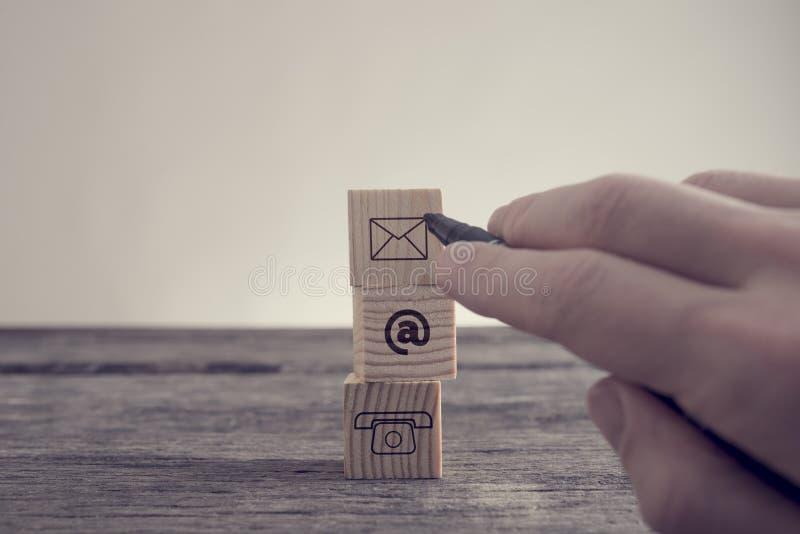 Kontaktsymbolumschlag am Zeichen und am Telefon stockfotos