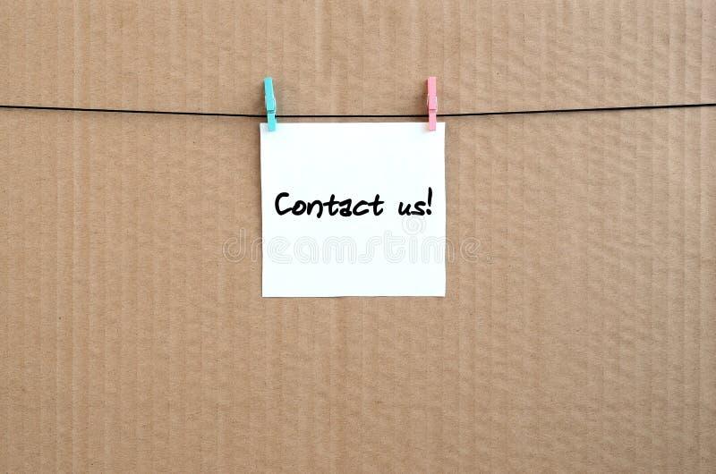 Kontaktuje się my! Notatka napisze na białym majcherze który wiesza z a obrazy stock