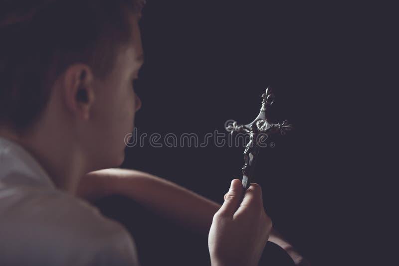 Kontemplacyjny nastoletni chłopak Trzyma Ozdobnego krzyż fotografia royalty free