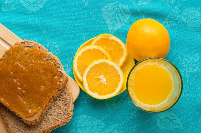 Kontinental frukost med orange fruktsaft, bröd och driftstopp arkivfoton