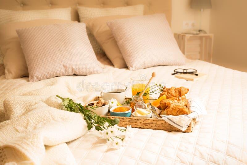 Kontinental frukost på säng i elegant sovruminre royaltyfria bilder