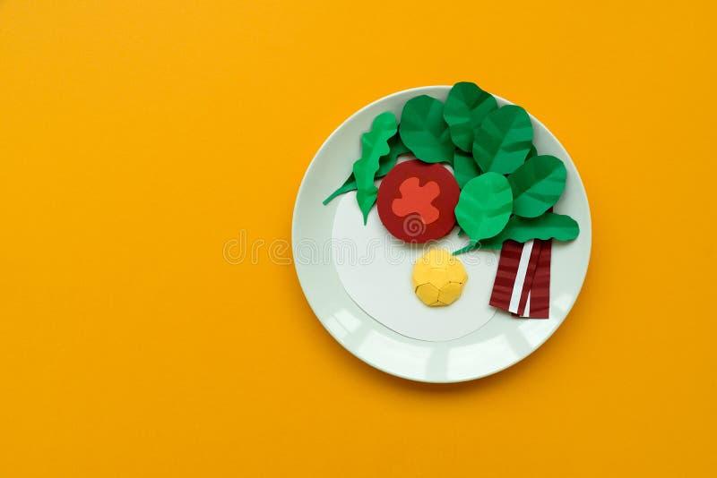 Kontinental frukost som g?ras fr?n papper: stekt ?gg, tomat, bacon, spenat och arugula p? gul bakgrund Minsta id?rikt, royaltyfri foto