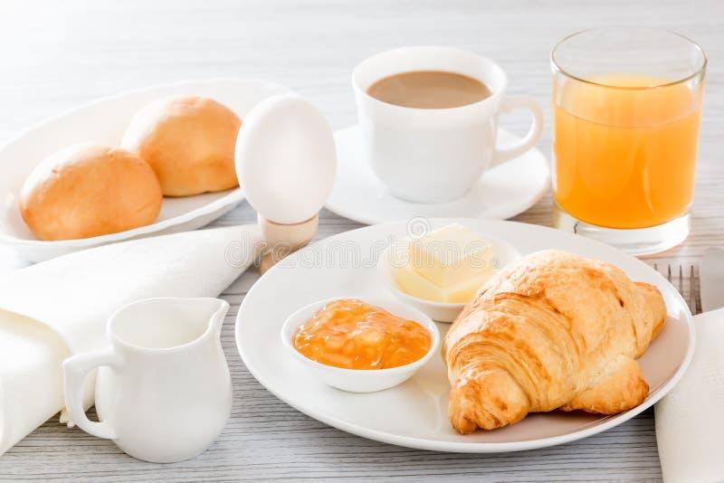 Kontinentales Frühstück mit einem Hörnchen, gekochtes Ei Kaffee oder Tee mit Milch, ein Glas Saft, Brötchen, Butter, Stau lizenzfreie stockbilder