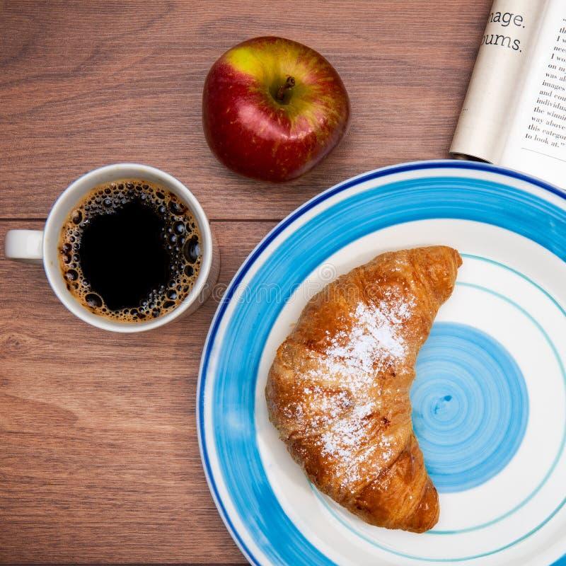 Kontinentales Frühstück mit Kaffee, frischen Hörnchen, Frucht und guter Zeitschrift lizenzfreies stockbild