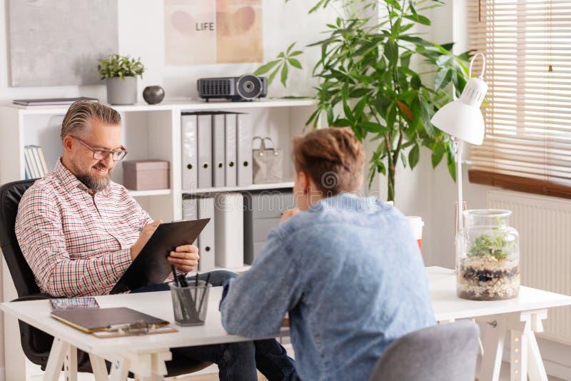 Kontochef och ung man under jobbintervju i liten firma arkivfoto