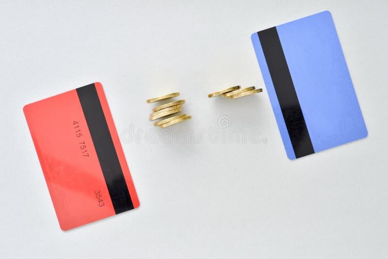 Kontokort är i färgerna av att bo korall och blått med skinande gula mynt som symboliserar det elektroniska utbytet av pengar arkivbilder