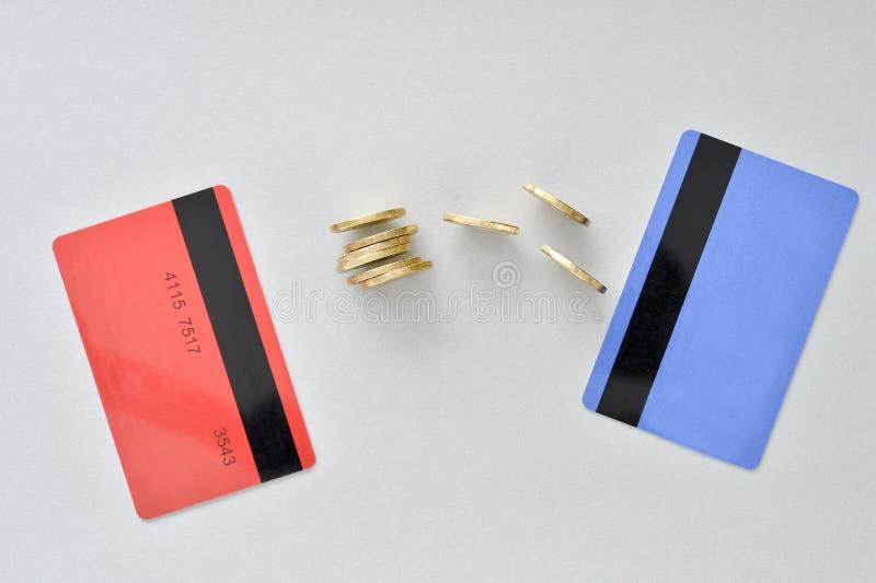 Kontokort är i färgerna av att bo korall och blått med skinande gula mynt som symboliserar det elektroniska utbytet av pengar arkivfoton