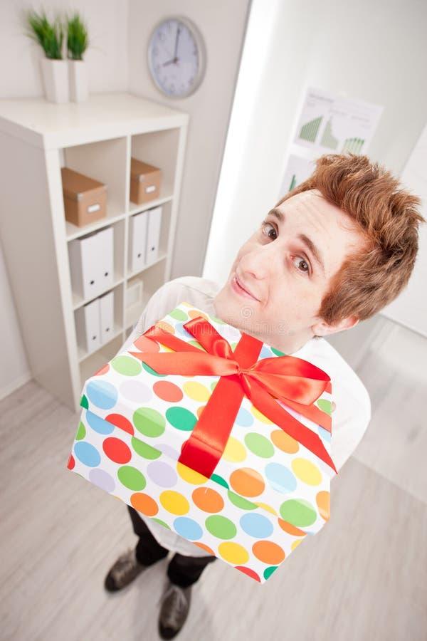 Kontorist med en stor gåva i bred vinkel royaltyfri bild