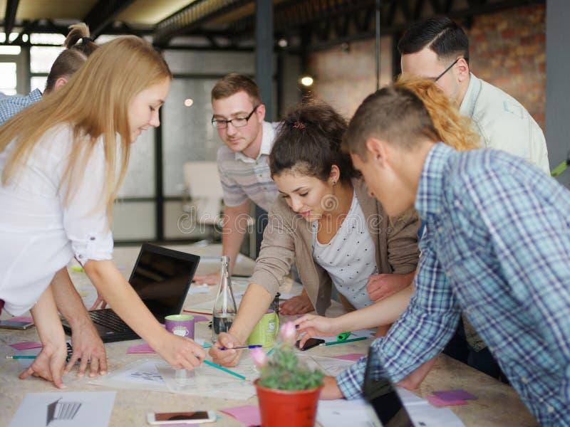 Kontorsarbetare bläddrar igenom och att diskutera projektet arkivfoto