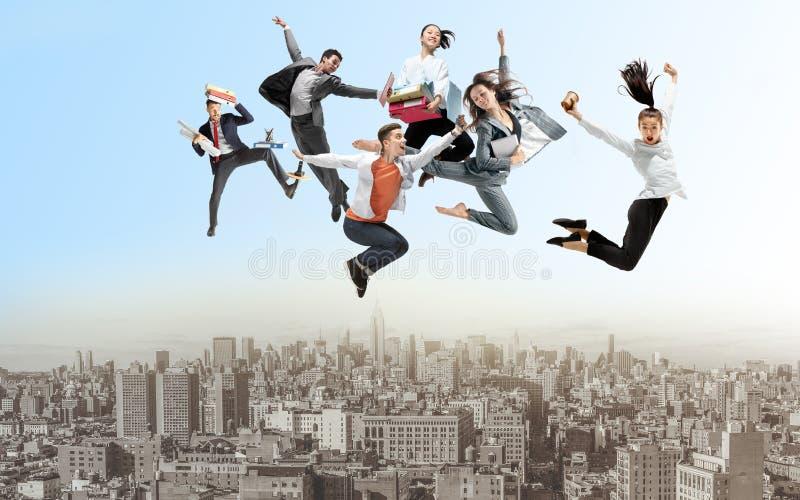 Kontorsarbetare eller balettdansörer som hoppar ovanför staden royaltyfri foto