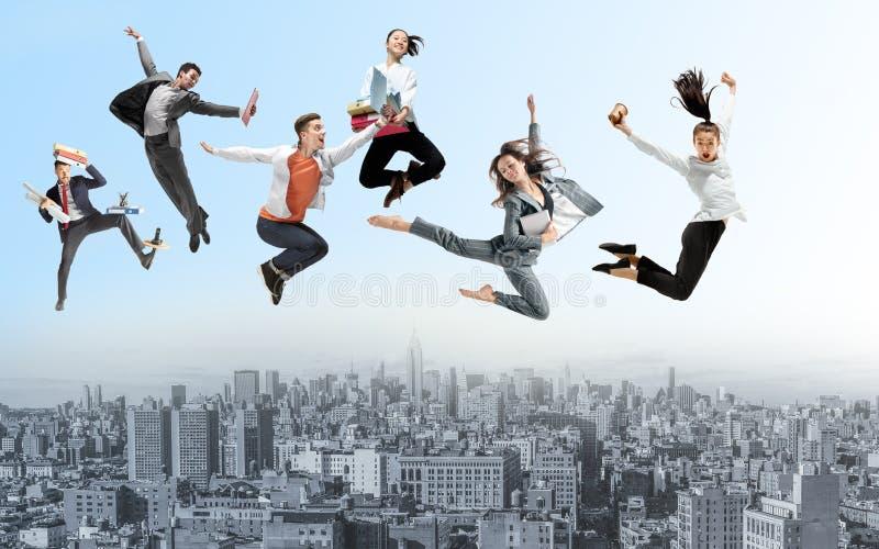Kontorsarbetare eller balettdansörer som hoppar ovanför staden arkivfoto