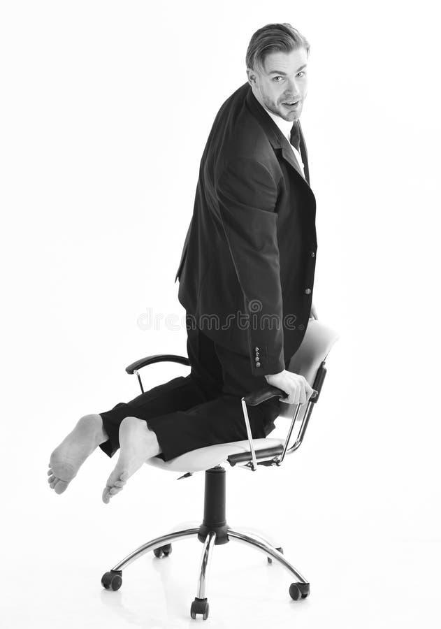 Kontorsarbetare med den gladlynta framsidan Dräkten för grabben ler och har i regeringsställning gyckel under kaffeavbrott Lyckli royaltyfri bild