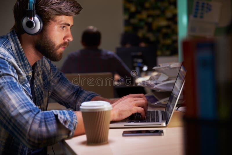 Kontorsarbetare med kaffe på skrivbordet som sent arbetar på bärbara datorn royaltyfri fotografi
