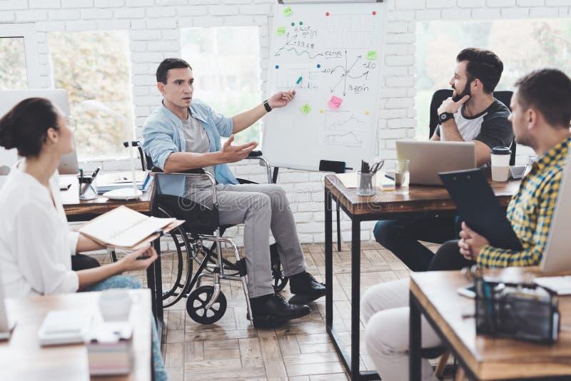 Kontorsarbetare och man i en rullstol som diskuterar affärsögonblick i ett modernt kontor arkivfoton