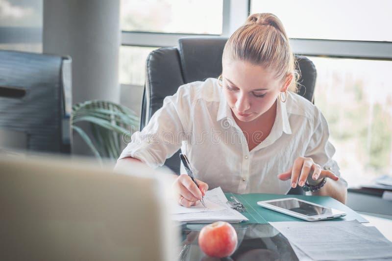 Kontorsarbetare på arbetsplatsen paper writing för flicka arkivbilder