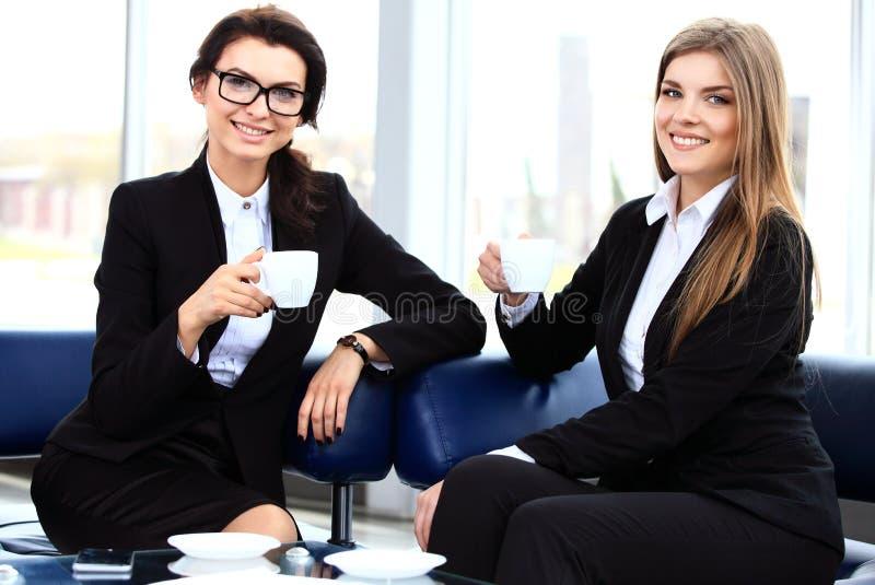 Kontorsarbetare på kaffeavbrottet, kvinna som tycker om att prata royaltyfri foto
