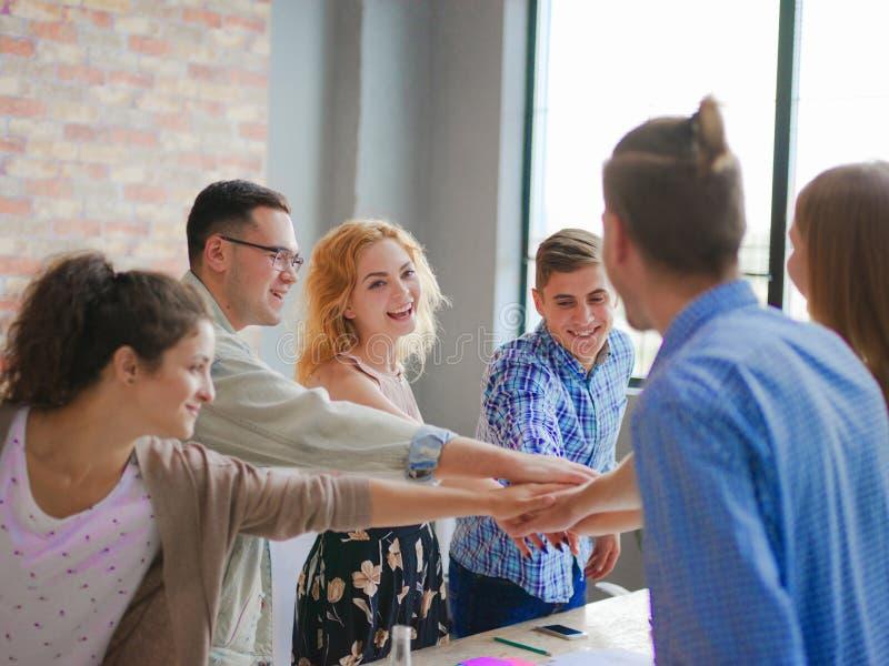 Kontorsarbetare sammanfogar händer för en bra start royaltyfri foto