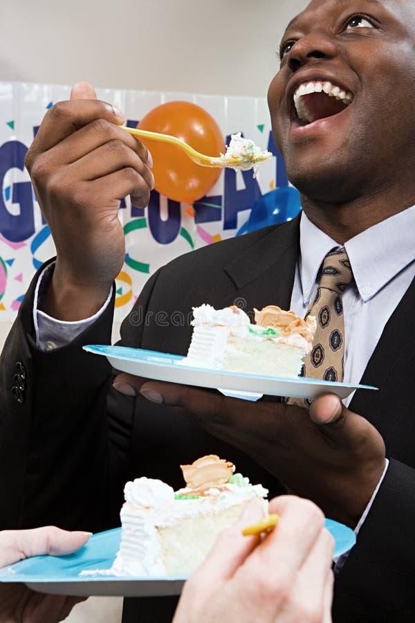 Kontorsarbetare som äter partikakan royaltyfria bilder