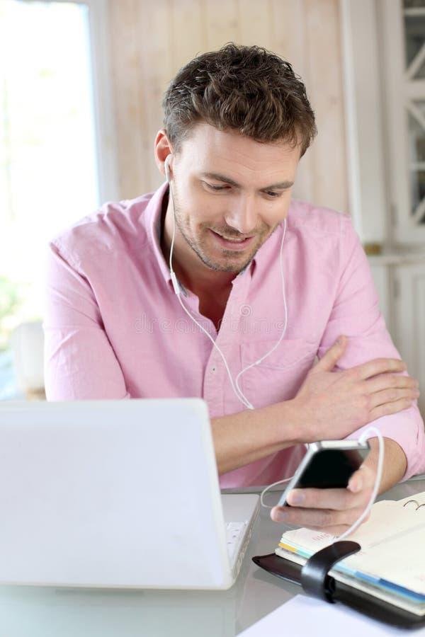 Kontorsarbetare som använder bärbara datorn och telefonen royaltyfri bild