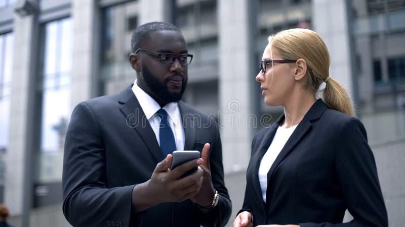 Kontorsarbetare som använder smartphonen och att smsa med affärspartnern som kontrollerar mejl royaltyfri foto