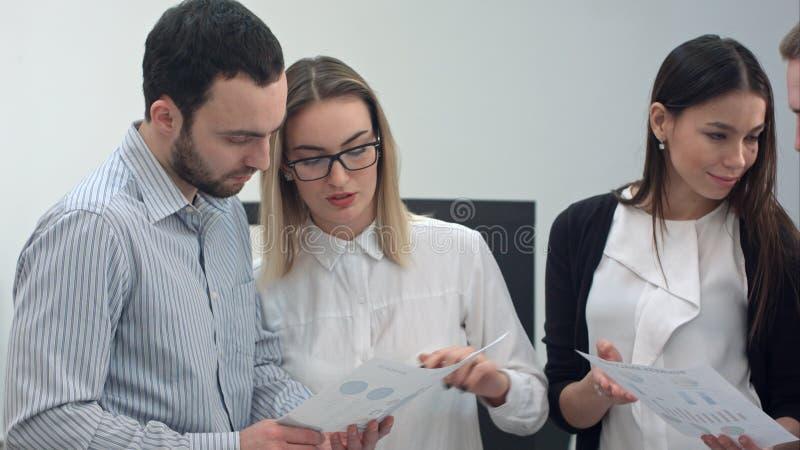 Kontorsarbetare som diskuterar presentationsmaterial arkivbilder