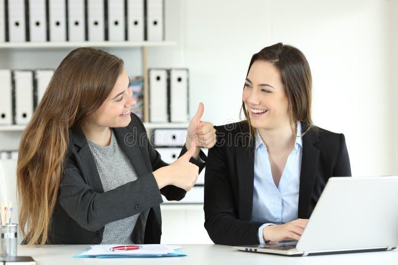 Kontorsarbetare som gratulerar hennes kollega arkivfoto