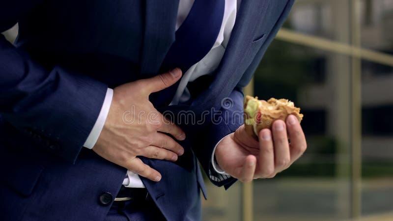 Kontorsarbetare som känner buk- obehag, medan äta den sjukliga hamburgaren fotografering för bildbyråer