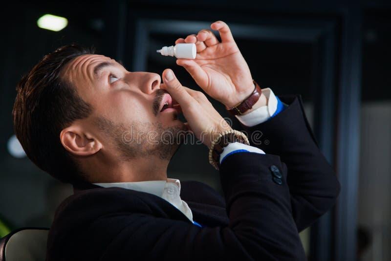 Kontorsarbetare som lider syndrommen för torrt öga, ögondroppar för konstgjorda revor royaltyfri foto