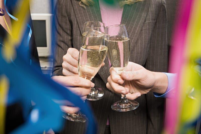 Kontorsarbetare som rostar med champagne royaltyfria bilder