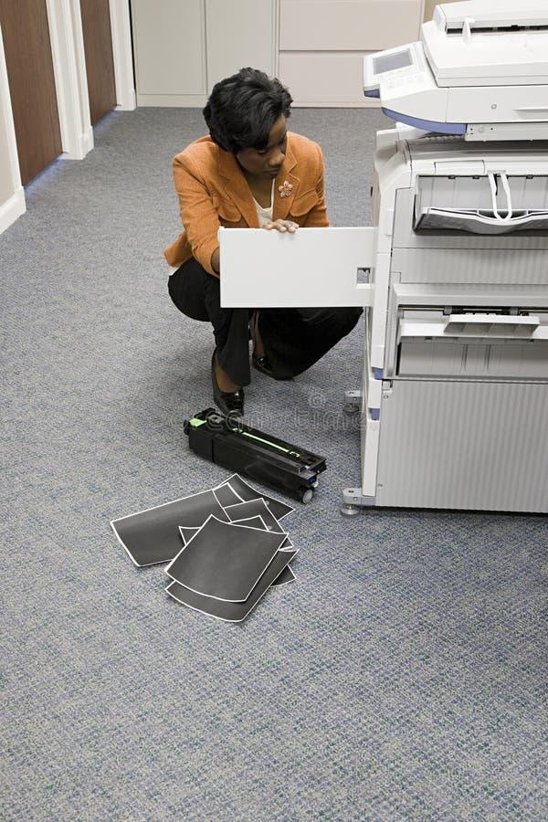 Kontorsarbetare som ser fotokopiatorn royaltyfri fotografi