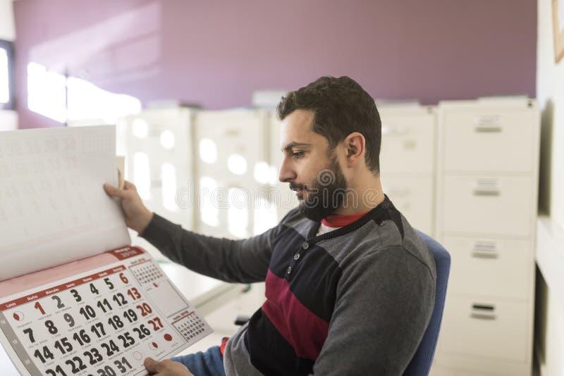 Kontorsarbetare som ser hans arbetskalender royaltyfria bilder