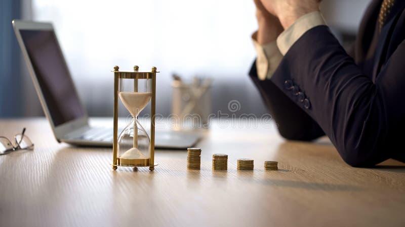 Kontorsarbetare som tänker om inkomst, sikt av sandglass och bunt av mynt royaltyfri bild