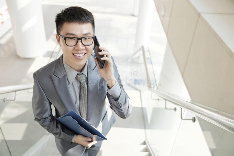 Kontorsarbetare som talar p? mobiltelefonen p? kontoret royaltyfria foton