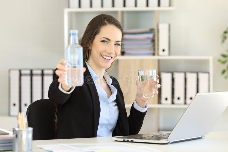 Kontorsarbetare som visar en flaska av vatten royaltyfri bild