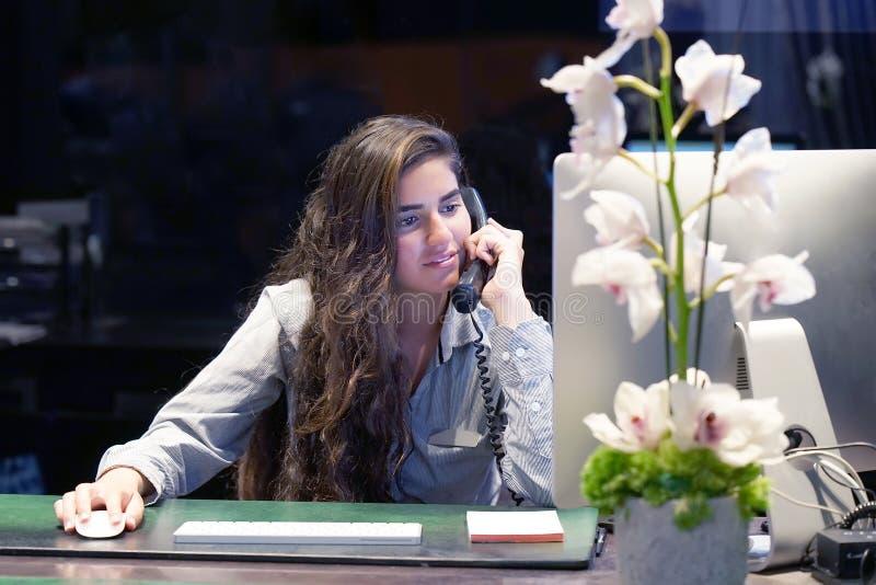 Kontorsarbetaren arbetar på tangentbordet Ett sammanträde för kvinnakontorsarbetare på skrivbordet och arbete med en dator royaltyfri fotografi