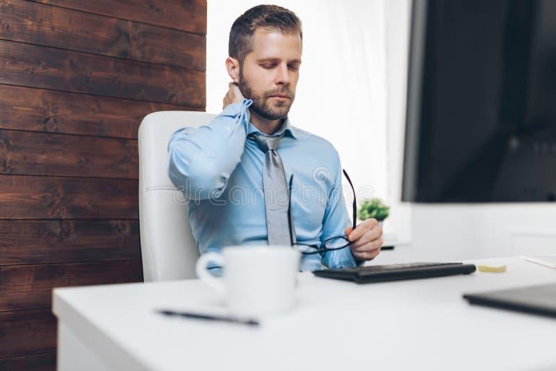 Kontorsarbetaren med smärtar från att sitta på skrivbordet hela dagen arkivbilder