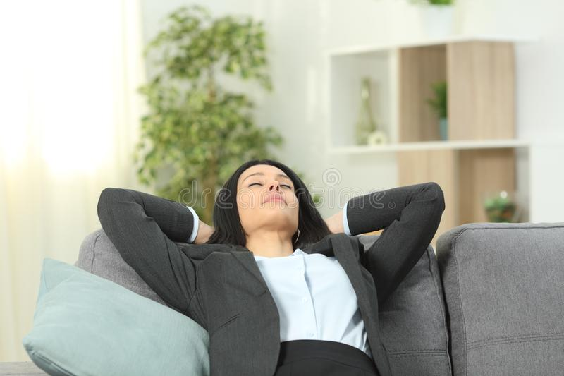 Kontorsarbetaren vilar på en soffa hemma efter arbete fotografering för bildbyråer
