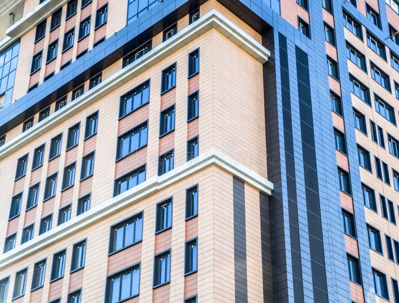 Kontorsbyggnad mång--våning byggnad Byggnad mot den blåa himlen med moln royaltyfri bild
