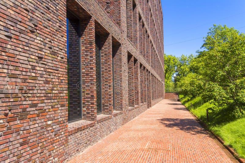Kontorsbyggnad som göras av tegelsten med stora Windows Dekorativt murverk genom att använda kurvor, icke-standard tegelstenar royaltyfri bild