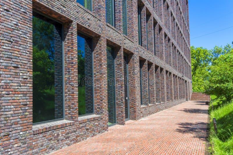 Kontorsbyggnad som göras av tegelsten med stora Windows Dekorativt murverk genom att använda kurvor, icke-standard tegelstenar royaltyfri foto