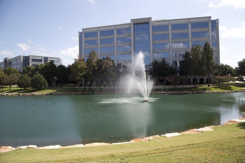 Kontorsbyggnader och härligt parkerar sikt arkivfoto