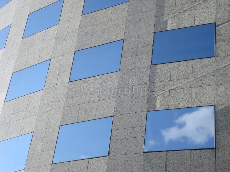 Kontorsbyggnadvägg med rektangulära fönster som reflekterar himlen royaltyfri bild